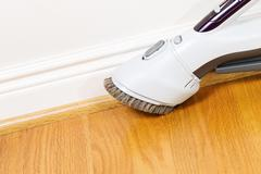 cleaning floor and trim work with vacuum cleaner - stock photo