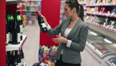 Beautiful woman in supermarket choosing wine HD - stock footage