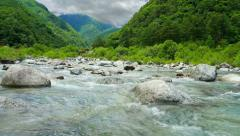 Mountain river with moving clouds in the background. Time lapse. Stock Footage