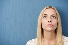 thoughtful young woman biting her lip - stock photo