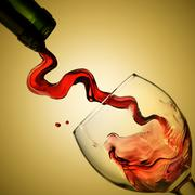 pouring red wine in goblet on yellow background - stock photo