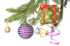 Christmas balls, gift and decoration on fir tree branch isolated on white Stock Photos