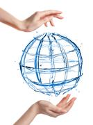 globe from water with human hand isolated on white - stock photo