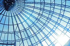 Modern glass roof with blue sky and sun Stock Photos