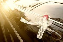 door of black wedding car with flower and ribbon - stock photo