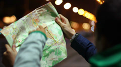 Two tourists looking for place on map, location finding night - stock footage