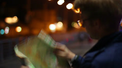 Male looking for route in tourist map foreign city night Stock Footage