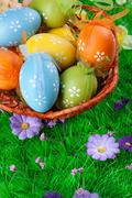color easter eggs in basket on the green grass - stock photo
