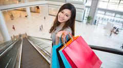beautiful young woman shopping in mall - stock photo