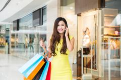 young woman shopping phoning in mall - stock photo