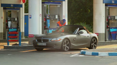 Service for rich, gas station timelapse blonde in elite car Stock Footage
