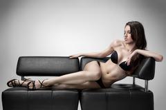 sexy woman in a black bikini swimsuit lies on the sofa - stock photo