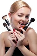 Young smiling woman with make up brushes isolated on white Stock Photos