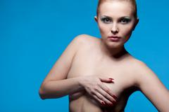 portrait of nude young woman on blue - stock photo