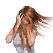 Woman with headphones and hair in motion on white Stock Photos