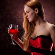 elegant woman with red hair holding wine glass - stock photo