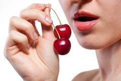 young woman with cherry isolated on white - stock photo