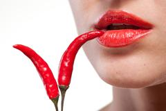 Young woman with chili pepper isolated on white Stock Photos