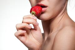 young woman biting strawberry isolated on white - stock photo