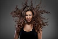 portrait of beautiful woman with curly hair in air - stock photo