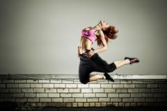 Girl jumping on the roof Stock Photos