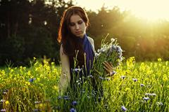 girl gathering flowers on sunset - stock photo