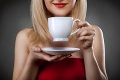 Woman in red holding cup and smiles Stock Photos