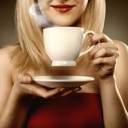 Stock Photo of woman in red holding cup and smiles