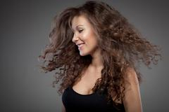 portrait of smiling woman with curly hair - stock photo