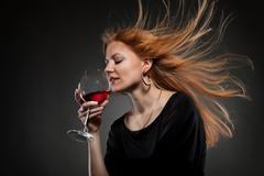 woman with red hair holding wine glass - stock photo