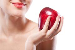 Portrait of smiling woman holding red apple isolated on white Stock Photos