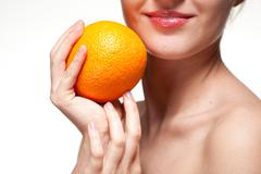 young woman with orange isolated on white - stock photo