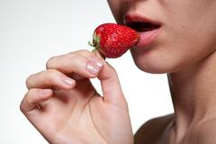 Young woman biting strawberry isolated on white Stock Photos