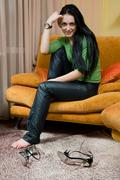 Attractive smiling woman relaxing and sitting on sofa at home Stock Photos