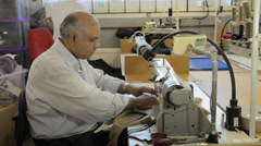 Man working on a sewing machine in a dressmaker's factory Stock Footage