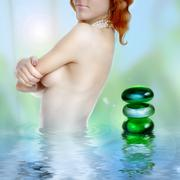 Beautiful young woman in water with stylized spa stones Stock Photos
