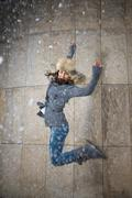 Young woman jumping in fur hat against the wall Stock Photos