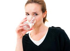 woman drinking water against white background - stock photo