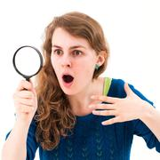 young woman through a magnifying glass - stock photo