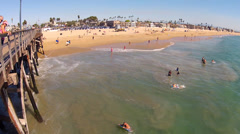 People Playing In Surf By Seal Beach CA Pier Stock Footage