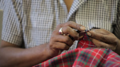 Man's hands sewing with scissors in a dressmaker's factory Stock Footage