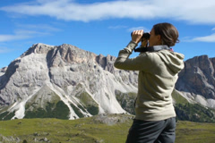 Hiker looking in binoculars enjoying view during hiking trip NTSC Stock Footage