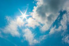 The sun shines on blue sky and clouds. Stock Photos