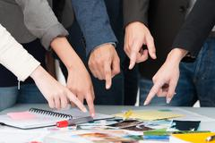 Stock Photo of business team pointing to a universal choice