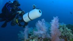 Scuba diver swimming with scooter over coral reef Stock Footage