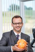 Businessman holding a piggy bank Stock Photos