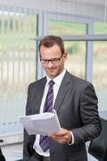 confident businessman reading a document - stock photo