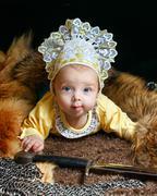 Baby, fox pelt and sword Stock Photos