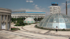Young modern woman walks past glass yurts in Almaty, central square, Kazakhstan Stock Footage