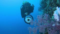 Scuba diver swimming with scooter along the coral reef Stock Footage